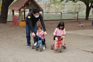 『三輪車で遊ぶパパと子どもたち』の画像